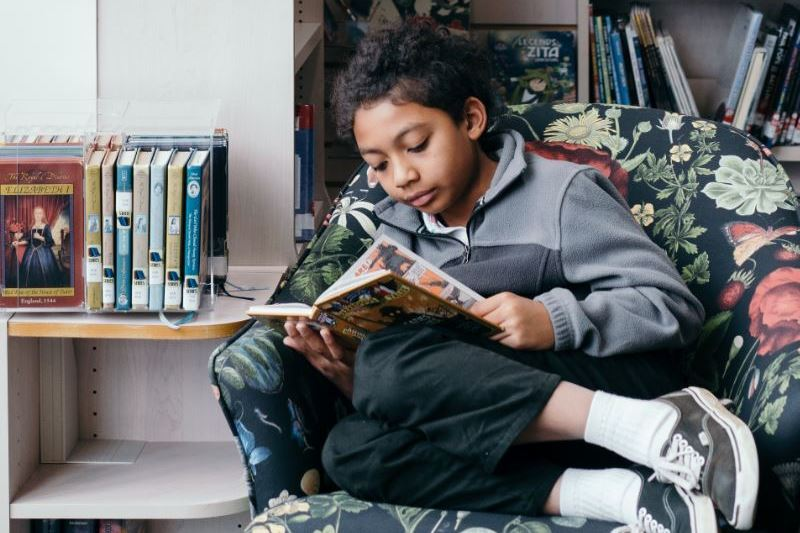 boy reading book on chair