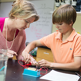 Teacher with student working on science project